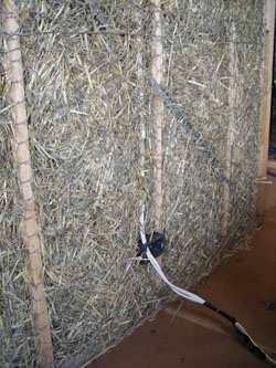 Internal stuffed strawbale wall with electrical rough-in visible.