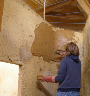Applying the final coat of straw bale render using a trowel.