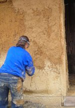 'Cobbing' is done by hand to fill in gaps before the second coat of render is applied.