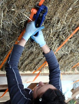 Tensioning a completed strawbale wall with a tensioning tool.